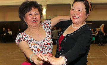 two women posing for the camera and dancing at the tea dance