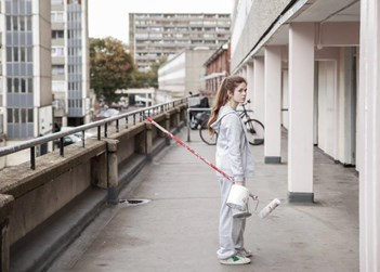 girl standing outdoors on a balcony of run down flats holding a paint roller and tin