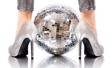 close up on woman wearing silver heeled shoes and a disco ball placed between them