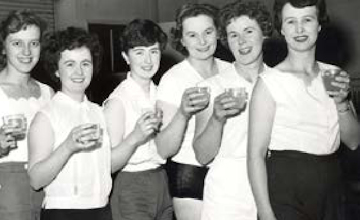 a group of women holding a drink and smiling at the camera