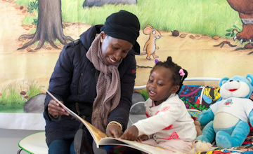 woman reading a book to a child