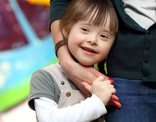 Young child with Downs Syndrome standing next to and holding the hand of her foster carer