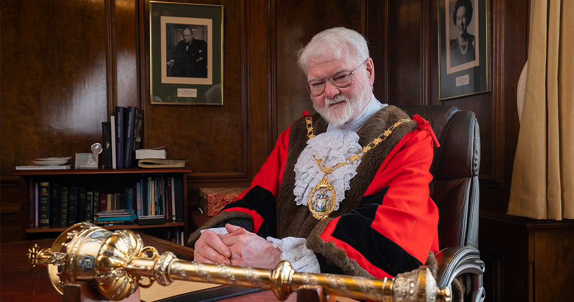 Roy Emmett sits behind his desk which has the ceremonial mace on it